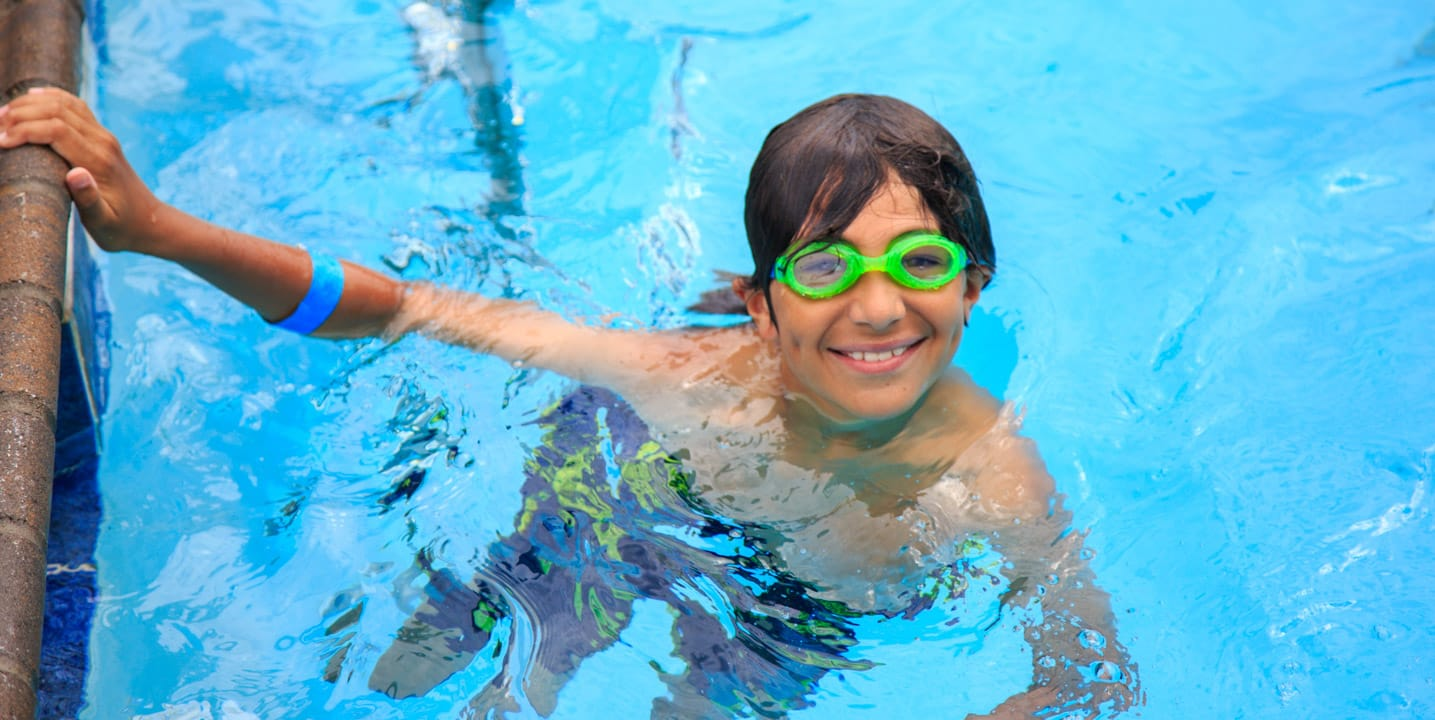 Boy in swimming pool with goggles