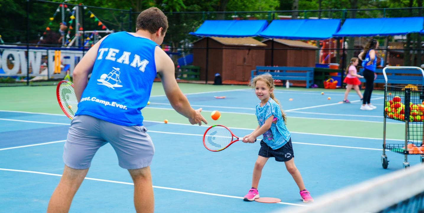 Staff and girl playing tennis